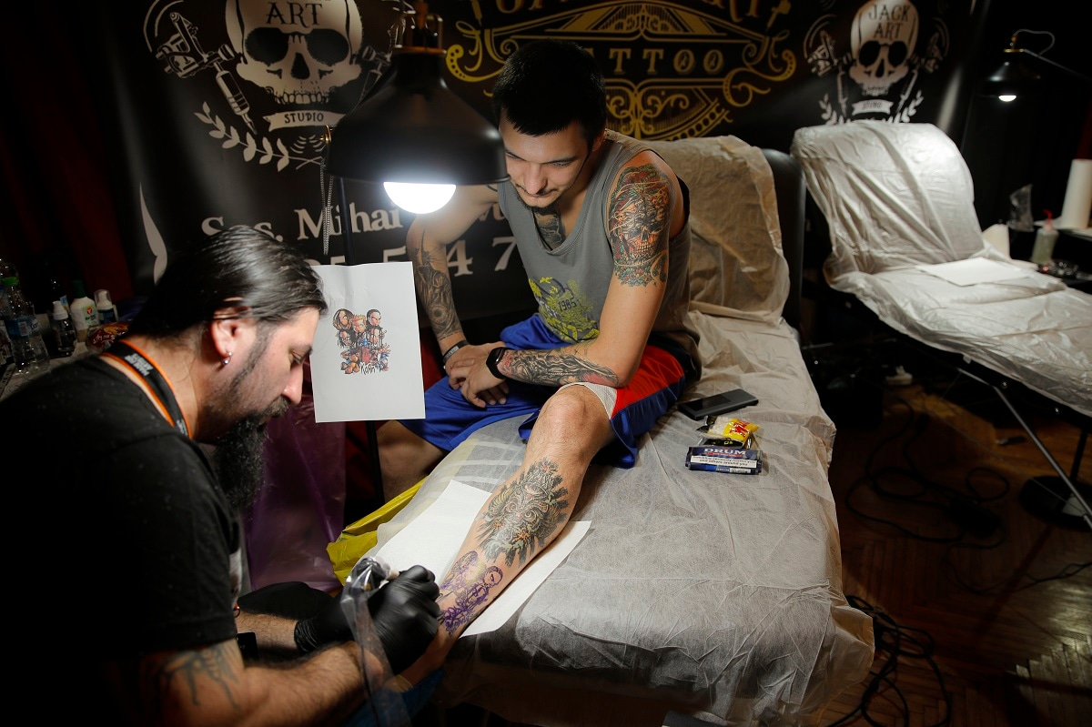 A man gets a new tattoo on his leg during the 10th International Tattoo Convention in Bucharest, Romania. (AP Photo/Vadim Ghirda)