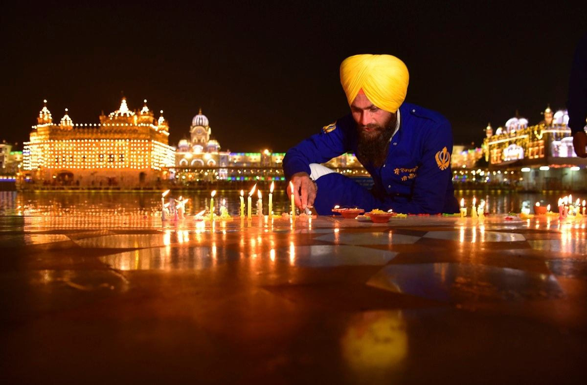 A Sikh man lights candles at an illuminated Golden Temple on the eve of the birth anniversary of Guru Nanak in Amritsar. (AP Photo/Prabhjot Singh, File)