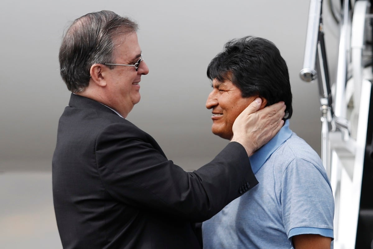 Mexican Foreign Minister Marcelo Ebrard, left, welcomes former Bolivian President Evo Morales upon his arrival to Mexico City. Mexico granted asylum to Morales, who resigned under mounting pressure from the military and the public after his re-election victory triggered weeks of fraud allegations and deadly protests. (AP Photo/Eduardo Verdugo)