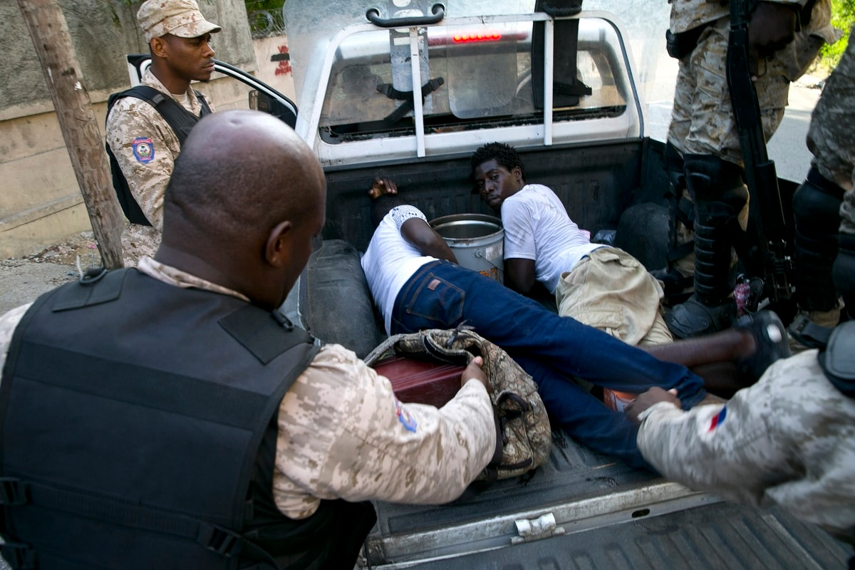 Police officers detain two men whom they claim stole an inverter battery during a protest to demand the resignation of President Jovenel Moise, in Port-au-Prince, Haiti. Anger over corruption, inflation and scarcity of basic goods, including fuel, has led to more than a month of demonstrations that have paralyzed the country as protesters demand the resignation of President Moise. (AP Photo/Dieu Nalio Chery)