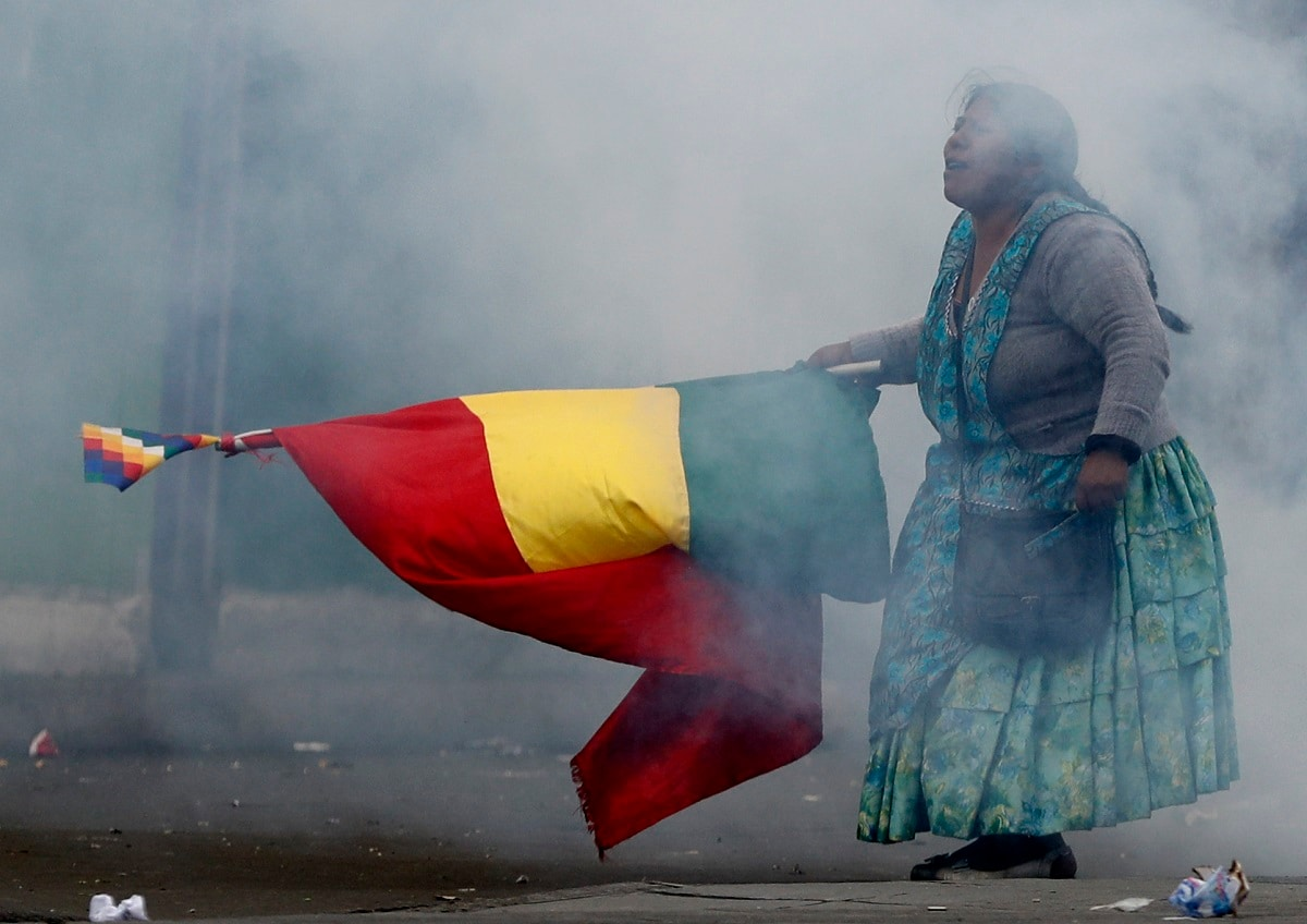 A supporter of former President Evo Morales holds a Bolivian flag during clashes with police in La Paz, Bolivia. Bolivia's new interim president Jeanine Anez faces the challenge of stabilizing the nation and organizing national elections within three months at a time of political disputes that pushed Morales to fly off to self-exile in Mexico after 14 years in power. (AP Photo/Natacha Pisarenko)