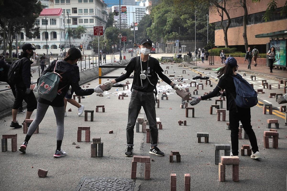 Protesters move bricks as they barricade a road near the Hong Kong Polytechnic University in Hong Kong. (AP Photo/Kin Cheung, File)