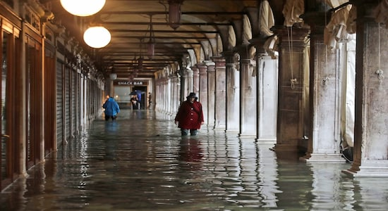 People wade through water in a flooded Venice, Italy, Nov. 12, 2019. (AP Photo/Luca Bruno)