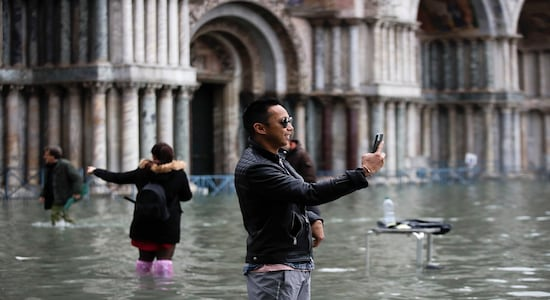 Tourists take pictures in a flooded St. Mark's Square, in Venice, Nov. 13, 2019. (AP Photo/Luca Bruno)