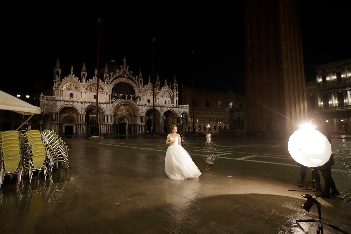 A woman wearing a bride dress poses for an early morning picture in St. Mark's Square in Venice. (AP Photo/Luca Bruno)