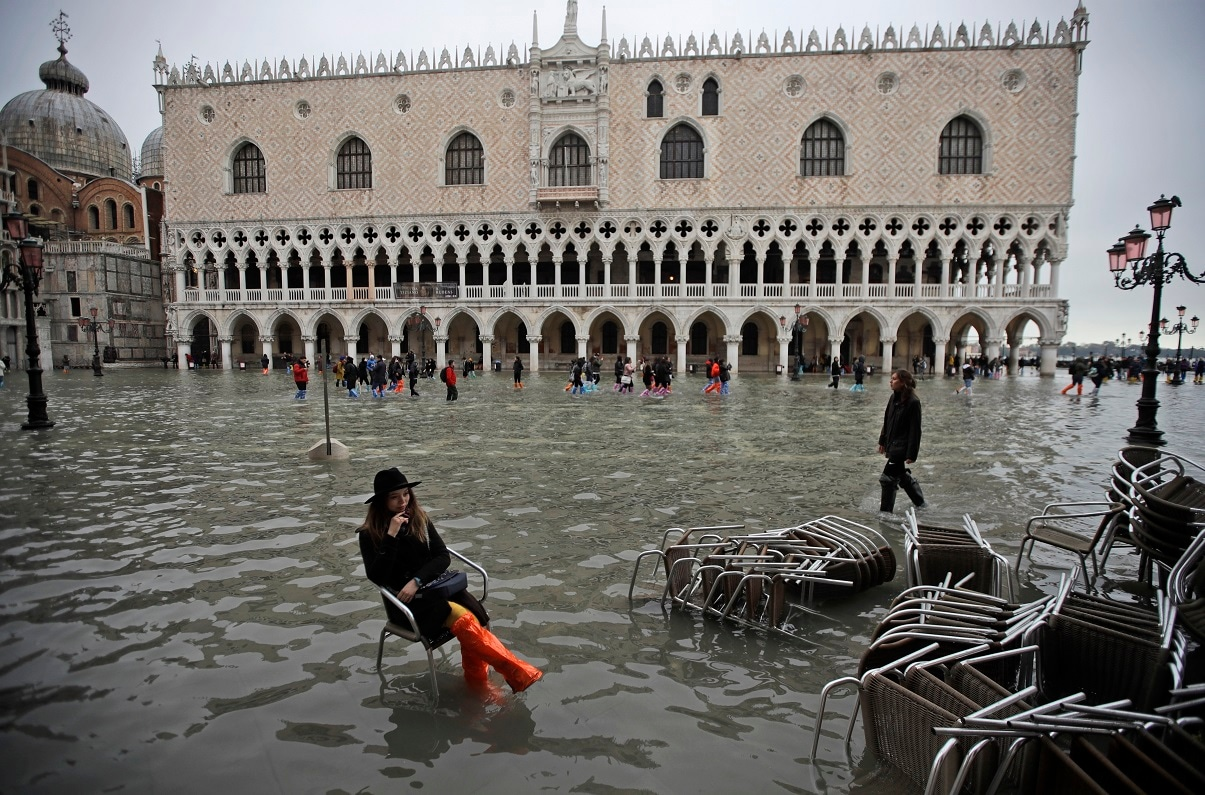 A woman sits in a chair in a flooded St. Mark's Square, in Venice. (AP Photo/Luca Bruno)