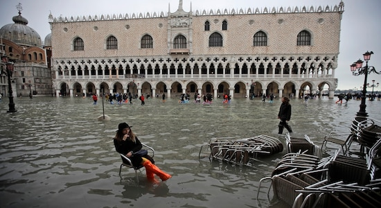 A woman sits in a chair in a flooded St. Mark's Square, in Venice, Nov. 13, 2019. (AP Photo/Luca Bruno)