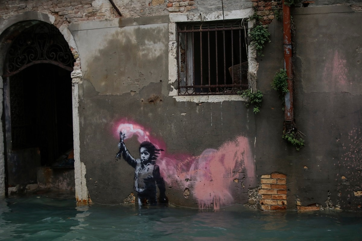 Banksy's migrant child mural is partially submerged in Venice. (AP Photo/Luca Bruno)