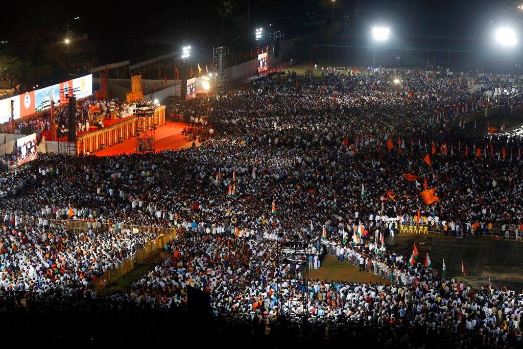 A crowd gathers to watch the swearing-in-ceremony of Shiv Sena party President Uddhav Thackeray as the chief minister of Maharashtra state at Shivaji Park in Mumbai, India, Thursday, Nov. 28, 2019. (AP Photo/Rajanish Kakade)
