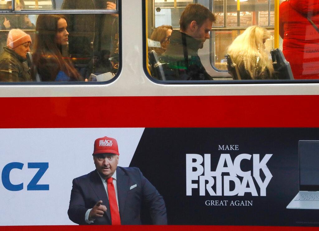 People sit on a tram advertising the Black Friday in Prague, Czech Republic, Thursday, Nov. 28, 2019. (AP Photo/Petr David Josek)