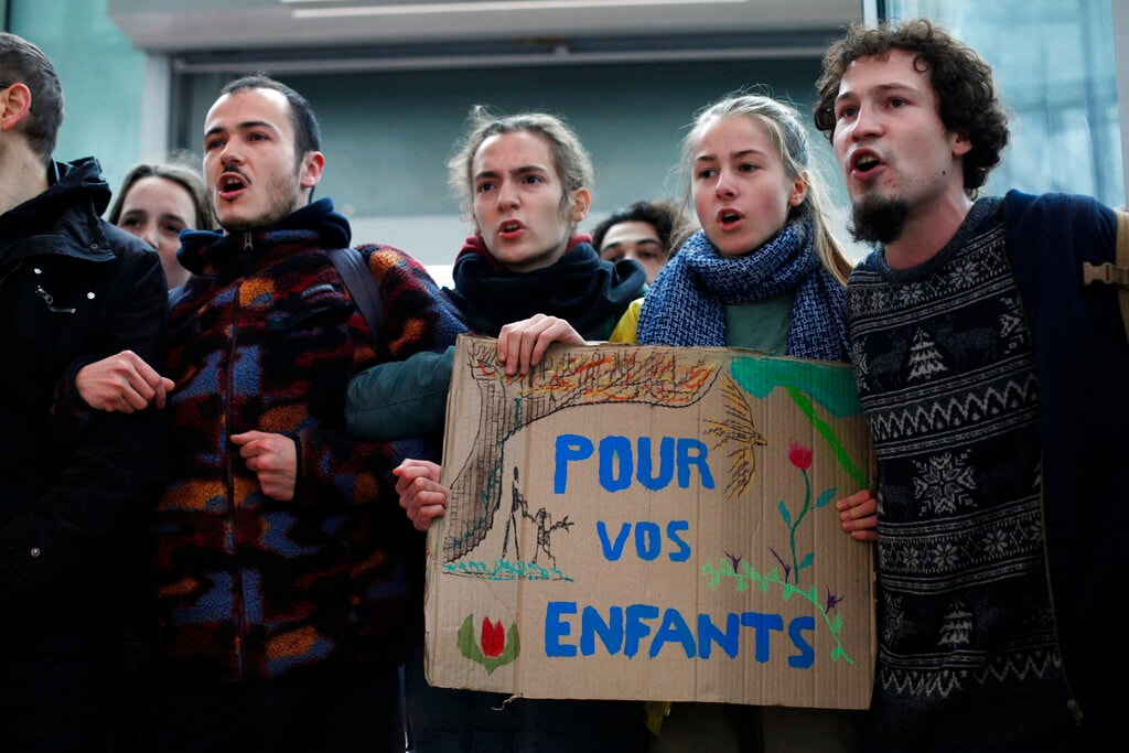 Activists block a shopping center, in the business district of Paris, La Défense, in Paris, Friday, Nov. 29, 2019. The placard reads « For your children » .(AP Photo/Thibault Camus)