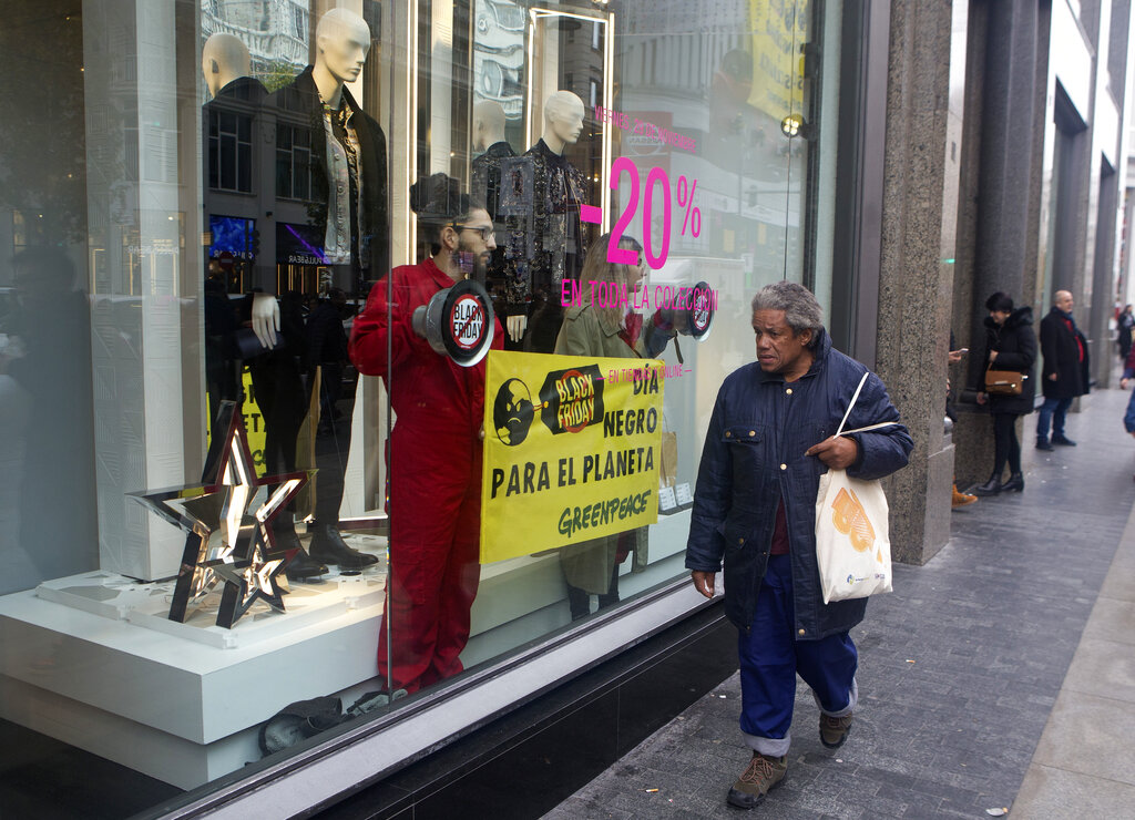 A woman walks past Greenpeace activists standing inside a store window display during a Black Friday sale in Madrid, Spain, Friday, Nov. 29, 2019. Banner reads ' Black day for the Planet'. (AP Photo/Paul White)
