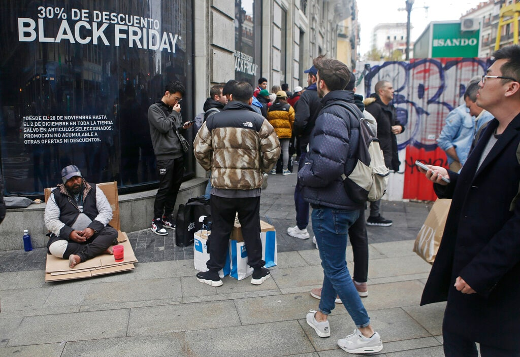 People queue outside a store during a Black Friday sale in Madrid, Spain, Friday, Nov. 29, 2019. (AP Photo/Paul White)