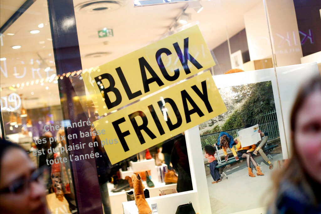 Women stand in front of a poster promoting the Black Friday in the business district of Paris, La Défense, in Paris, Friday, Nov. 29, 2019. (AP Photo/Thibault Camus)