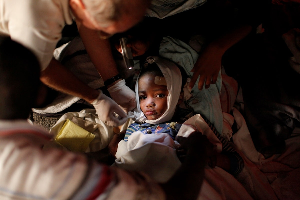 An injured child receives medical treatment after a 7.0 magnitude earthquake in Port-au-Prince, Haiti on January 13, 2010. REUTERS/Eduardo Munoz/File Photo