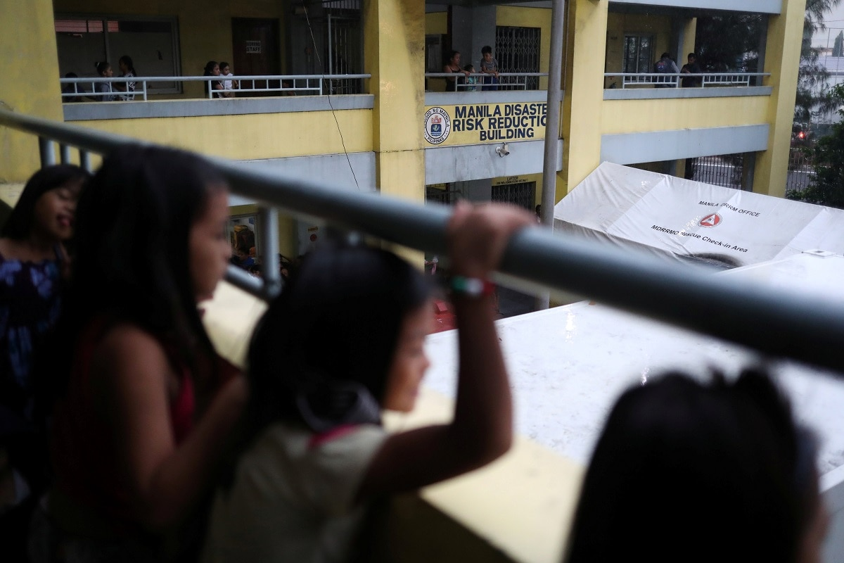 Children look on at the Delpan Evacuation Center after Typhoon Kammuri hit Metro Manila. Sustained winds of Kammuri weakened to 100 kilometres per hour (67 miles per hour), with gusts of up to 125 kph (78 mph) as it heads towards the South China Sea. It is set to leave the Philippines on Wednesday night, the state weather bureau said. REUTERS/Ann Wang