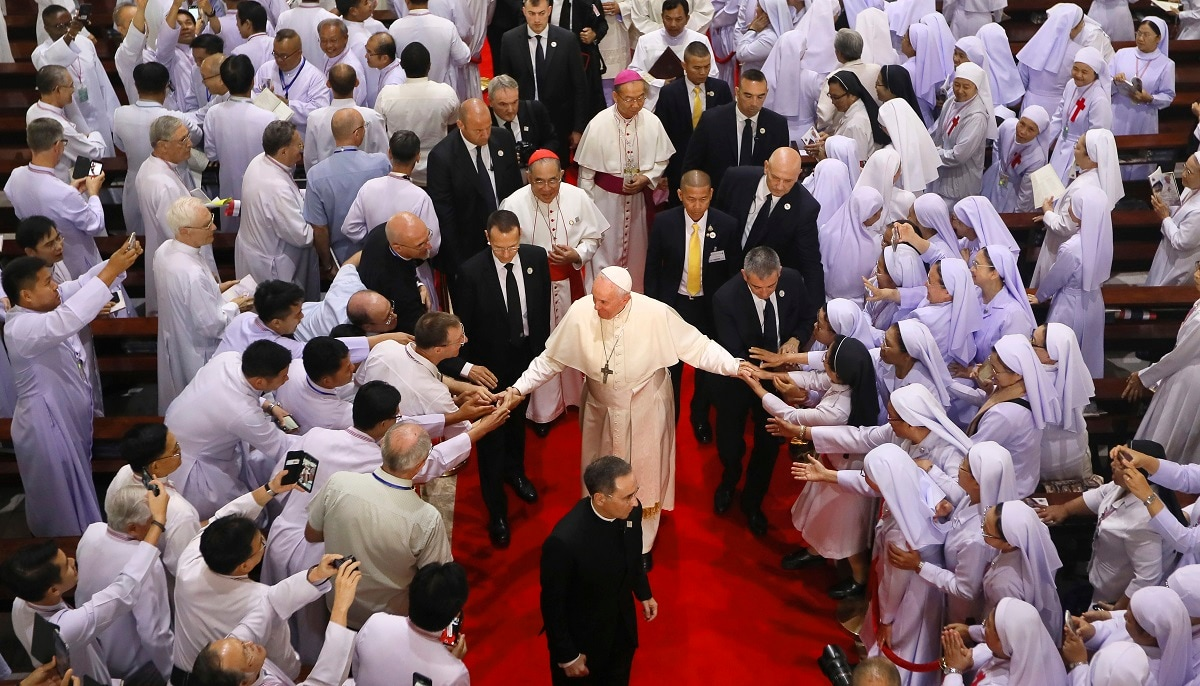 Priests, religious seminarians and Catechists touch the hands of Pope Francis as he leaves after meeting them at Saint Peter's Parish on the outskirts of Bangkok, Thailand. Pope Francis urged more efforts to combat the
