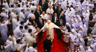 """In this Friday, Nov. 22, 2019, file photo, priests, religious seminarians and Catechists touch the hands of Pope Francis as he leaves after meeting them at Saint Peter's Parish on the outskirts of Bangkok, Thailand. Pope Francis urged more efforts to combat the """"humiliation"""" of women and children forced into prostitution as he began a busy visit Thursday to Thailand, where human trafficking and poverty help fuel the sex tourism industry. (AP Photo/Manish Swarup, File)"""