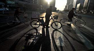 In this Tuesday, Nov. 26, 2019, file photo, the sun casts the shadows from cyclists as they cross the Mirae Scientist Street in downtown Pyongyang, North Korea. (AP Photo/Dita Alangkara, File)