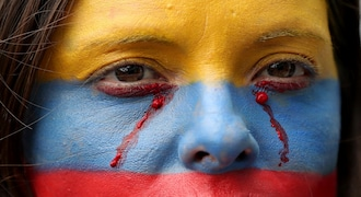 In this Nov. 27, 2019 photo, an anti-government demonstrator, her face painted with the colors of the Colombian national flag, takes part in a protest, in Bogota, Colombia. Thousands of people have protested in Colombia over the past week, voicing discontent with the government of President Ivan Duque. (AP Photo/Fernando Vergara)