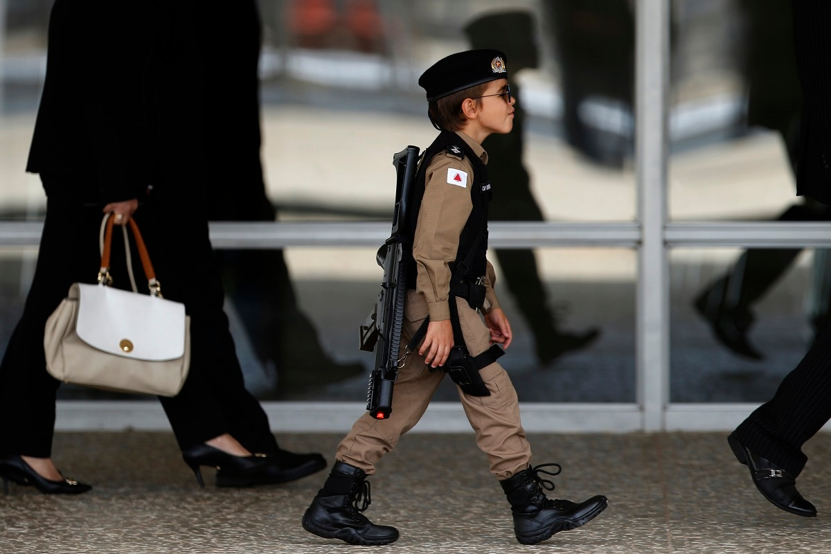 A boy dressed in a military police costume arrives to watch the Changing of the Guard at the Planalto Presidential Palace, in Brasilia, Brazil. (AP Photo/Eraldo Peres)