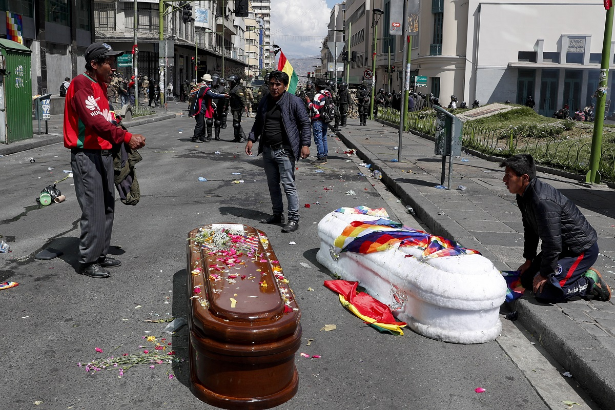 Coffins containing the remains of people killed during clashes between security forces and supporters of former President Evo Morales, lay in the middle of a street after police launched tear gas at a massive funeral procession to disperse anti-government protesters accompanying the coffins into La Paz, Bolivia. Bolivia has been in a state of turbulence since Morales resigned Nov. 10 after weeks of protests against him over a disputed vote that, according to an international audit, was marred by irregularities. (AP Photo/Juan Karita)