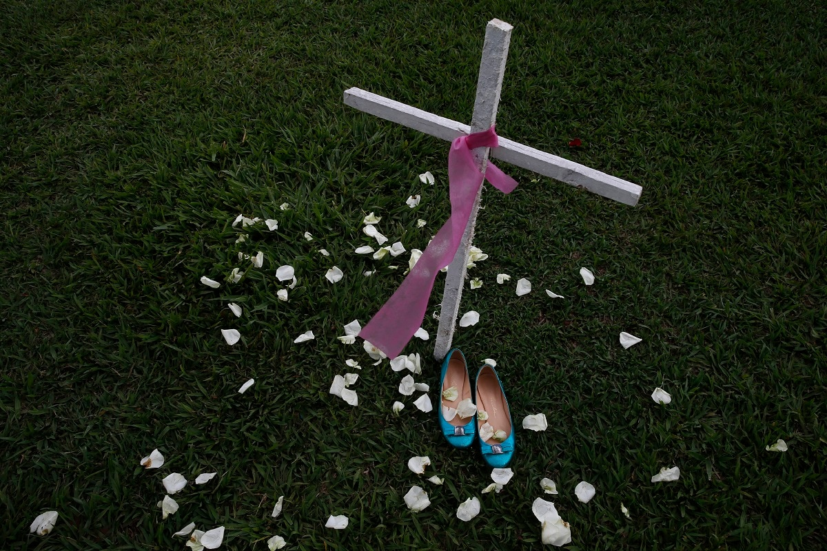 A cross and women's shoes are displayed in front of the National Congress headquarters to call the officials' attention to the high rate of violence against women in the country, in Brasilia, Brazil. Demonstrations are being held around the world on occasion of the International Day for the Elimination of Violence against Women. (AP Photo/Eraldo Peres)