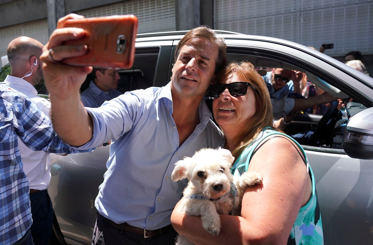 Presidential candidate for the National Party Luis Lacalle Pou, left, poses with a follower after voting in Canelones, Uruguay. Lacalle Pou was declared the winner by a narrow margin. (AP Photo/Matilde Campodonico)