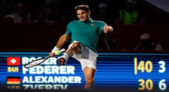 In this Nov. 23, 2019 photo, Roger Federer of Switzerland jokes around, juggling a tennis ball with his foot, during an exhibition tennis match against Germany's Alexander Zverev, at Plaza de Toros bullring in Mexico City. Saturday's match was the fourth stop in a tour of Latin America by the tennis greats. (AP Photo/Rebecca Blackwell)