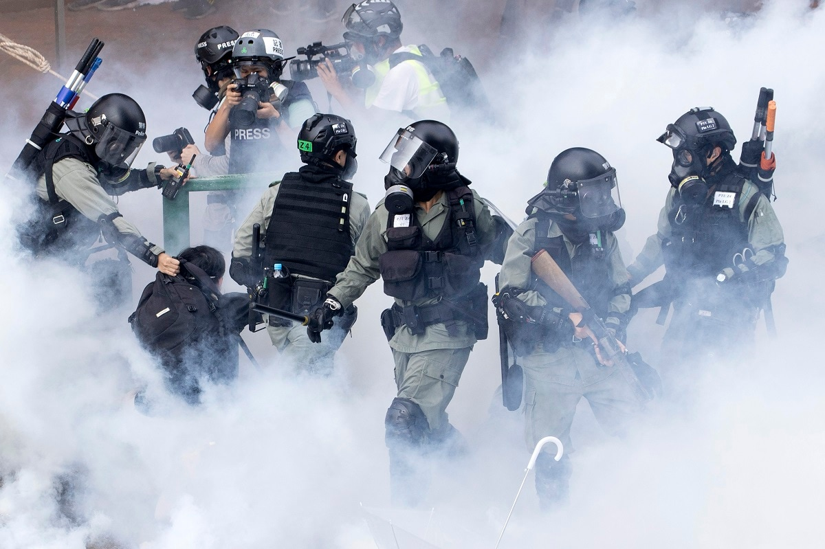 Police in riot gear move through a cloud of smoke as they detain a protester at the Hong Kong Polytechnic University in Hong Kong. Hong Kong police fought off protesters with tear gas and batons Monday as they tried to break through a police cordon that is trapping hundreds of them on a university campus. (AP Photo/Ng Han Guan, File)