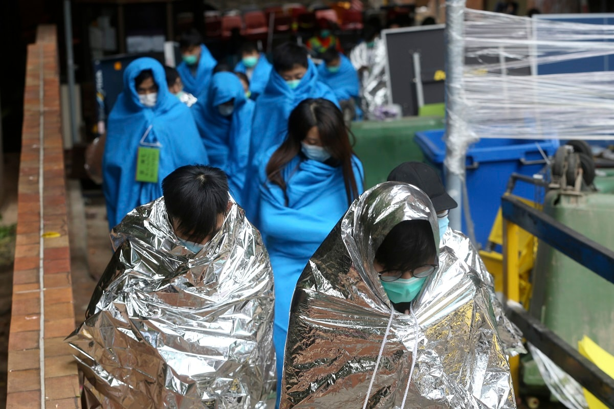 Injured protesters huddle under blankets as they walk at the Hong Kong Polytechnic University in Hong Kong. About 100 anti-government protesters remained holed up at a Hong Kong university Tuesday as a police siege of the campus entered its third day. (AP Photo/Achmad Ibrahim, File)