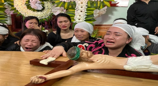 In this Saturday, Nov. 30, 2019, file photo, relatives of Bui Thi Nhung weep next to Nhung's casket at the family home in the village of Do Thanh, Vietnam. The body of 19-year old Nhung was among the last remains of the 39 Vietnamese who died while being smuggled in a truck to England last month that were repatriated to their home country on Saturday. (AP Photo/Hau Dinh, File)