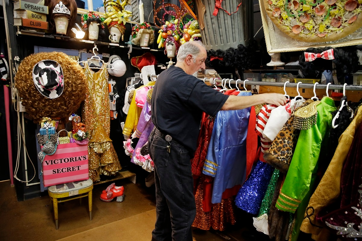 Stage manager John Camajani looks through the numerous costumes hanging in the backstage dressing room of the musical