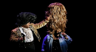 """In this Wednesday, Dec. 4, 2019 photo, singers James Brown and Tina Turner are portrayed JM Appleby, left, and Renee Lubin, right, during a performance of the musical """"Beach Blanket Babylon"""" in San Francisco. The campy small San Francisco show that's been a must-see for tourists and locals alike for more than 45 years, making it the nation's longest continuously running musical revue, is closing its curtain. Its final performance is set for New Year's Eve. (AP Photo/Eric Risberg)"""