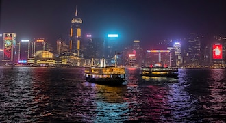 In this Friday, Dec. 13, 2019, file photo, the lights of Hong Kong Island are reflected in the water as Star Ferry boats cross the harbor from Kowloon, in Hong Kong. Despite six months of ongoing pro-democracy protests in Hong Kong, day to day life continues as normal in much of the city. (AP Photo/Mark Schiefelbein, File)
