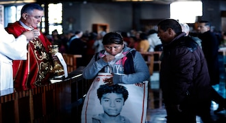 The Bishop of Chilpancingo, Guerrero state, Salvador Rengel, receives the family members of 43 missing students from the Isidro Burgos rural teachers college, carrying posters of their missing loved ones, during Mass at the Basilica of Guadalupe in Mexico City, Thursday, Dec. 26, 2019. Family members continue to call for justice five years after the Ayotzinapa students were allegedly taken from buses by local police and turned over to a drug gang. (AP Photo/Marco Ugarte)