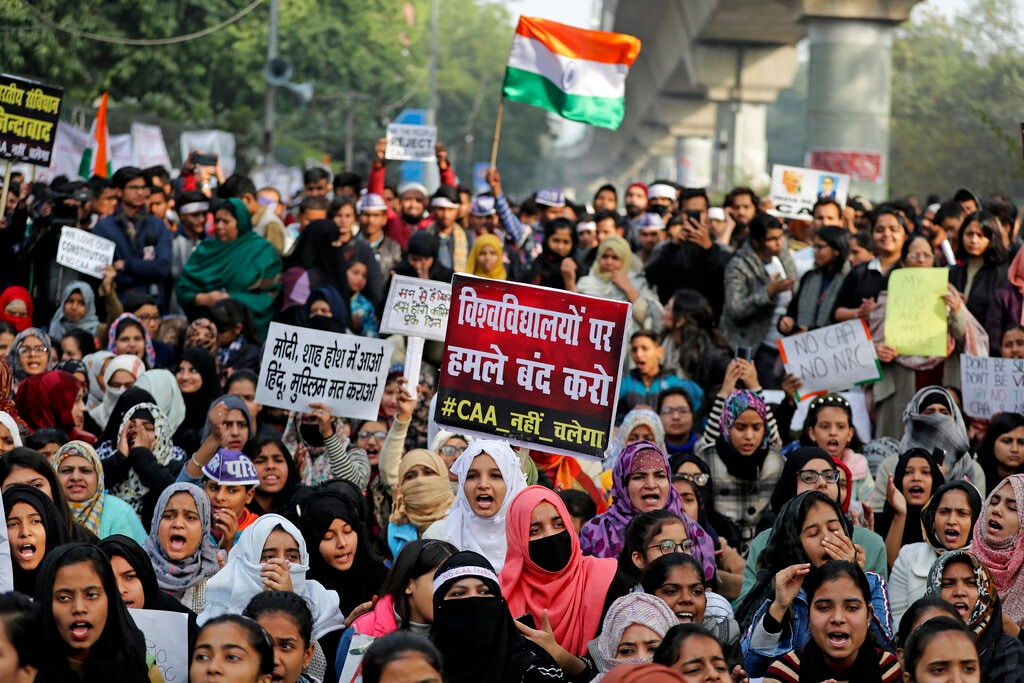 "Indian students of the Jamia Millia Islamia University and locals participate in a protest demonstration against a new citizenship law in New Delhi, India, Saturday, Dec. 21, 2019. Critics have slammed the law as a violation of India's secular constitution and have called it the latest effort by the Narendra Modi government to marginalize the country's 200 million Muslims. Modi has defended the law as a humanitarian gesture. Placard center reads ""Stop attacking universities."" (AP Photo/Altaf Qadri)"