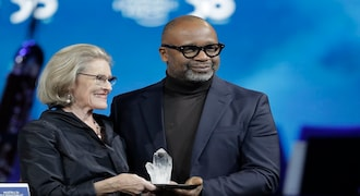 Artist Theaster Gates, from the United States, receives a Crystal Award from Hilde Schwab, Chairwoman and Co-Founder of the World Economic Forum's World Arts Forum, during the ceremony for the Crystal Awards at the annual meeting of the World Economic Forumin Davos, Switzerland, Monday, Jan. 20, 2020. The 50th annual meeting of the forum will take place in Davos from Jan. 21 until Jan. 24, 2020. (AP Photo/Markus Schreiber)