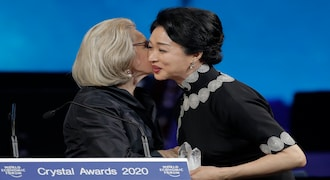 Dancer and coreographer Jin Xing, from China, receives a Crystal Award from Hilde Schwab, Chairwoman and Co-Founder of the World Economic Forum's World Arts Forum, during the ceremony for the Crystal Awards at the annual meeting of the World Economic Forumin Davos, Switzerland, Monday, Jan. 20, 2020. The 50th annual meeting of the forum will take place in Davos from Jan. 21 until Jan. 24, 2020. (AP Photo/Markus Schreiber)