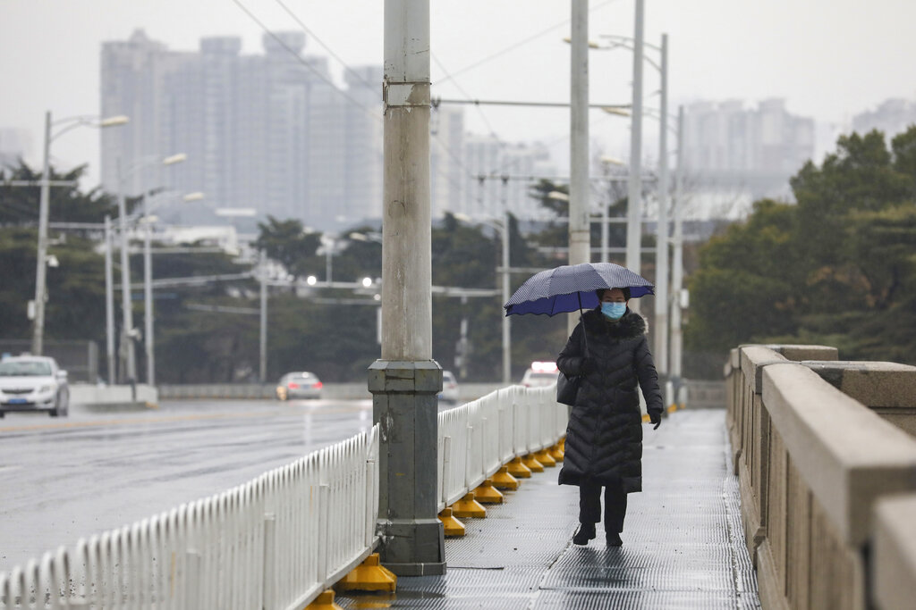 A woman wearing a face mask walks across a bridge in Wuhan in central China's Hubei province, Saturday, Jan. 25, 2020. The virus-hit Chinese city of Wuhan, already on lockdown, banned most vehicle use downtown and Hong Kong said it would close schools for two weeks as authorities scrambled Saturday to stop the spread of an illness that is known to have infected more than 1,200 people and killed 41, according to officials. . (Chinatopix via AP)