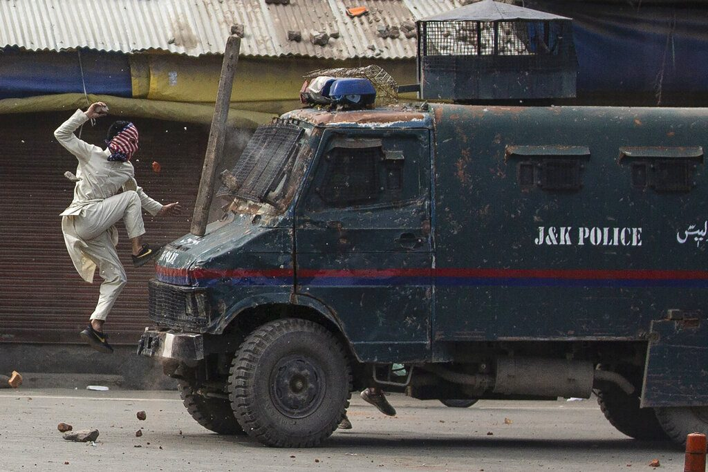 A masked Kashmiri protester jumps on the bonnet of an armored vehicle of Indian police as he throws stones at it during a protest in Srinagar, May 31, 2019. (AP Photo/Dar Yasin)