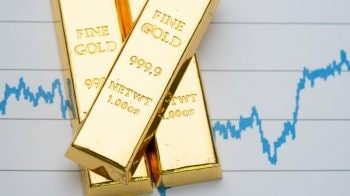 Gold rises on hopes of rates staying low, firm yields cap gains